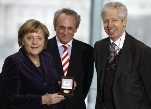 German Chancellor Merkel poses with a medal for the media after she was awarded by Prince Nikolaus of Liechtenstein, vice president of the European Coudenhove-Kalergi association Hoechtl of Austrian People's Party at the Chancellery in Berlin